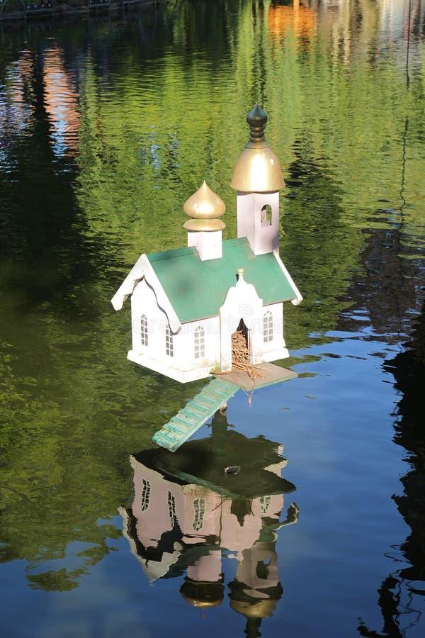 Reizendes kleines Haus für Ente auf dem See stockfotografie