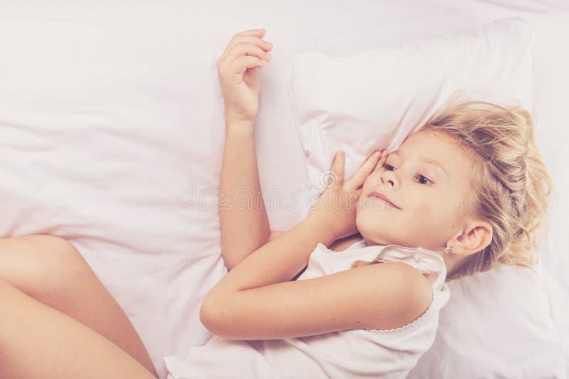 Reizendes kleines Mädchen, das auf dem Bett schläft lizenzfreies stockbild