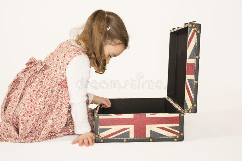 Reizendes kleines Mädchen, das inneren rettro Koffer schaut lizenzfreie stockbilder