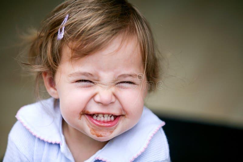 Reizendes kleines Mädchen, das lustiges Gesicht macht lizenzfreies stockbild