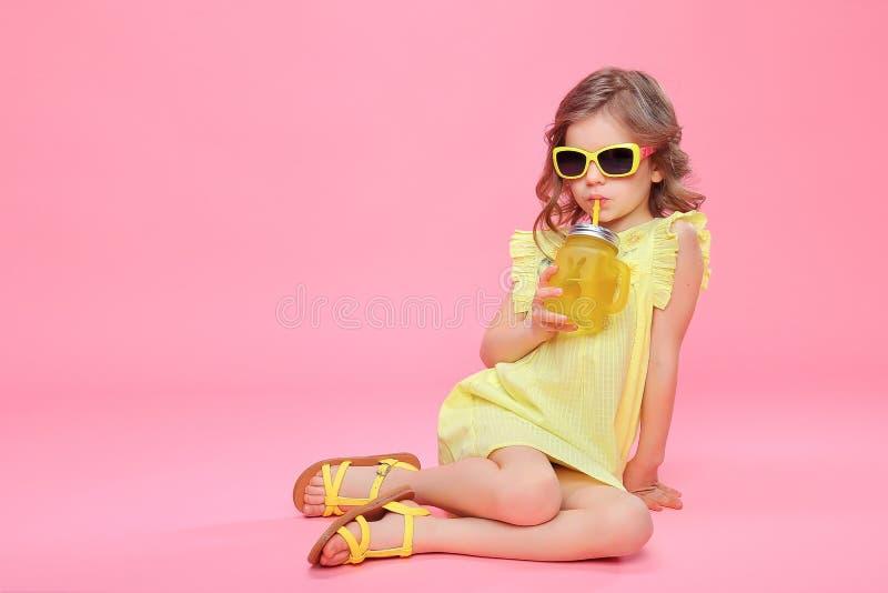 Reizendes kleines Mädchen in der Sommerausstattung mit Getränk lizenzfreie stockbilder