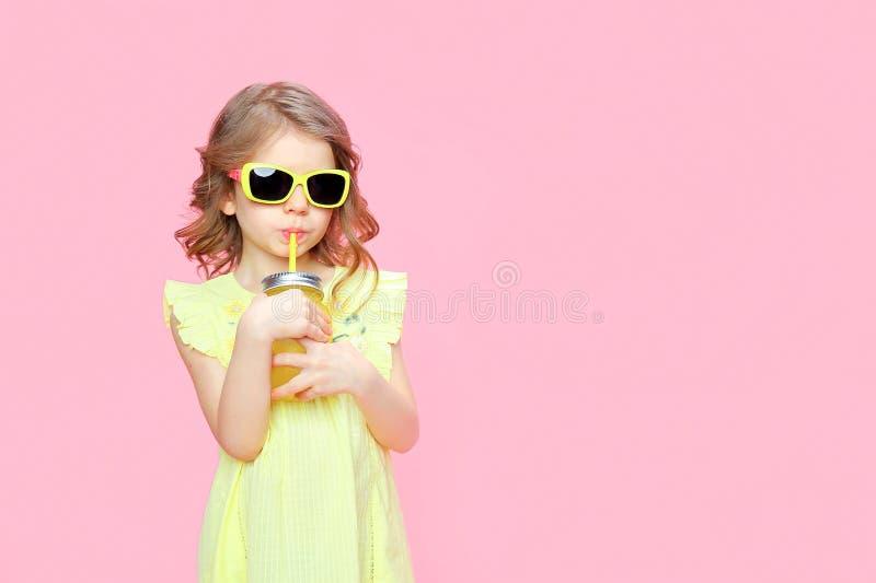 Reizendes kleines Mädchen in der Sommerausstattung mit Getränk stockbild
