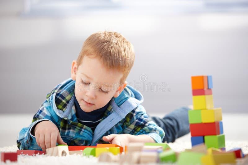 Reizendes Kleinkind, das zu Hause mit Gebäudewürfeln spielt stockfoto
