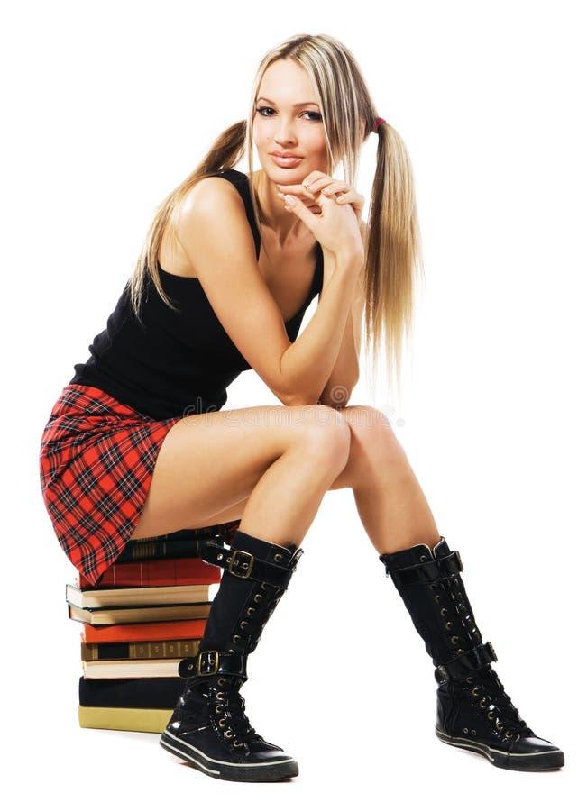 Reizendes Kursteilnehmermädchen, das auf einem Stapel Büchern sitzt stockfoto