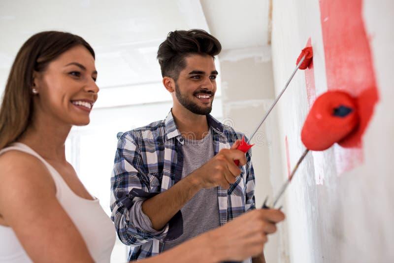 Reizendes lächelndes glückliches Paar, das neues Haus malt lizenzfreie stockbilder