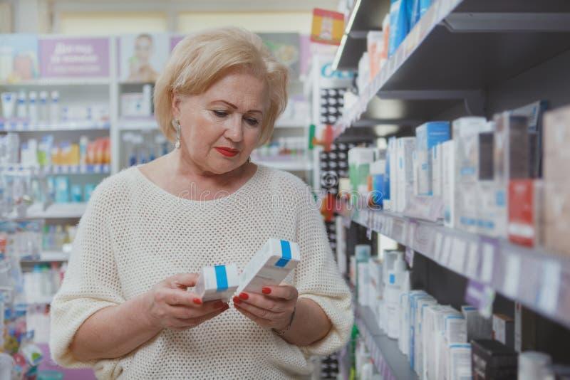 Reizendes ?lteres Fraueneinkaufen am Drugstore lizenzfreies stockfoto