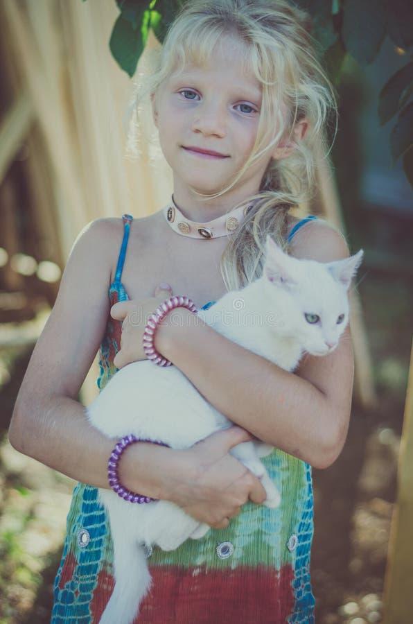 Reizendes Mädchen, das eine schöne kleine weiße Katze streichelt lizenzfreie stockfotos