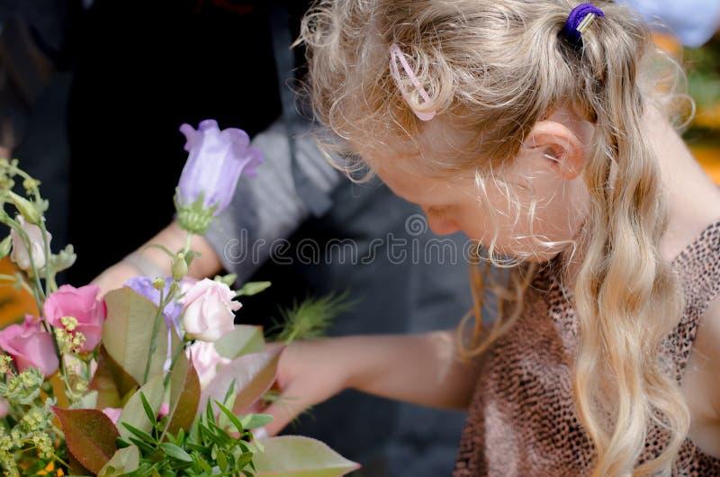 Reizendes Mädchen, das für Floristenberuf sich vorbereitet stockbild