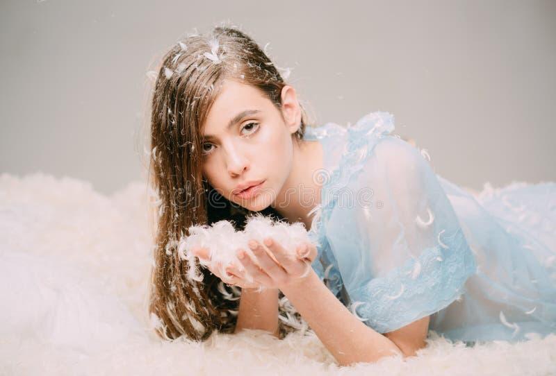 Reizendes Mädchen mit dem langen Brunettehaar, das Handvoll kleine Federn hält Netter weiblicher Jugendlicher im blauen Spitzenac stockfoto