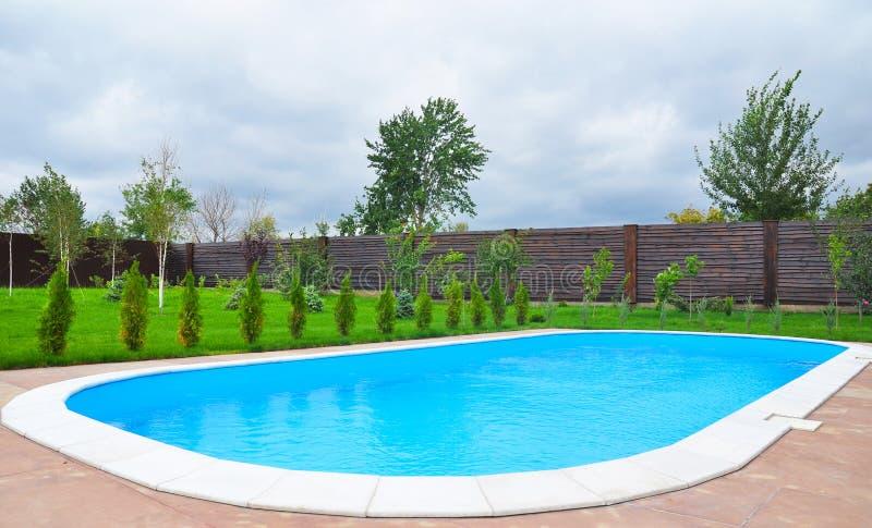 Reizendes Pool im Garten im Hinterhof gegen bewölkten Himmel lizenzfreies stockbild