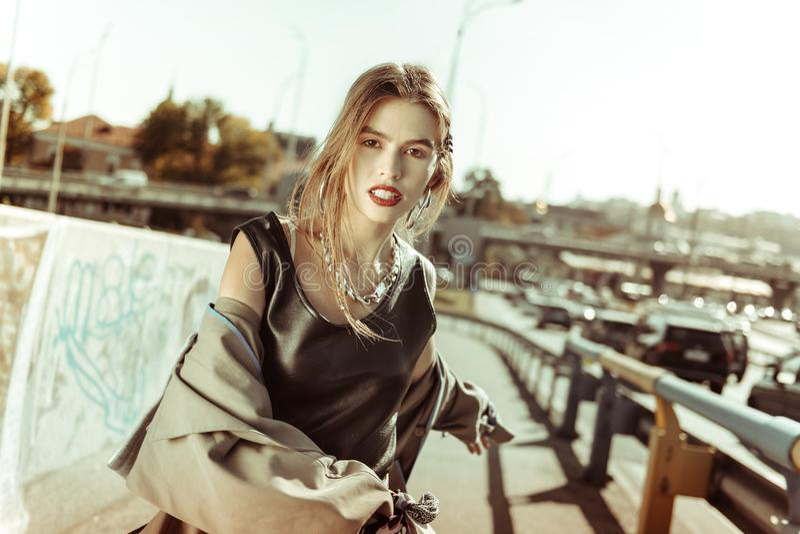 Reizendes tragendes Bündel junger Dame Zusätze während der Fotoaufnahme stockfoto