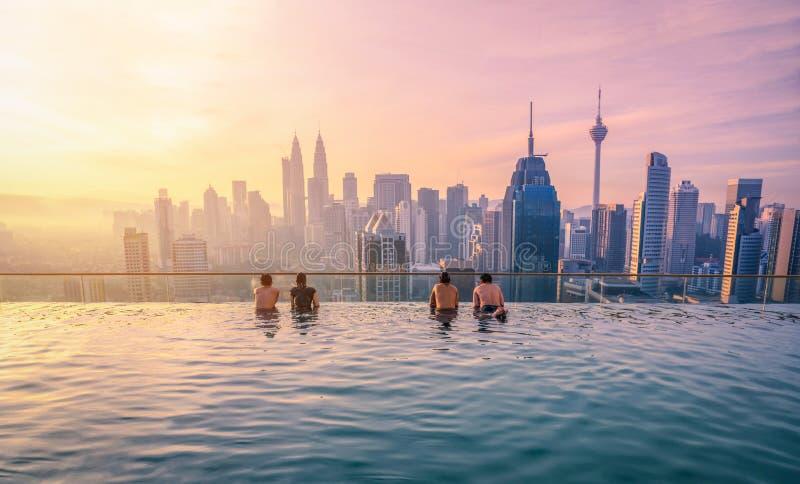 Reiziger die de stad van Kuala Lumpur van de meningshorizon in zwembad op de dakbovenkant van hotel zonsopgang in Kuala Lumpur, M stock afbeelding