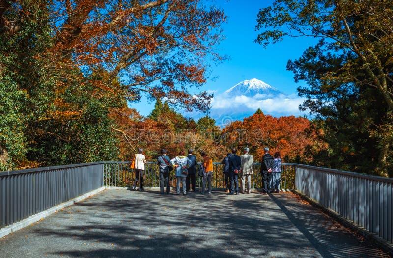 Reiziger die MT kijken Fuji en het kleurrijke de herfstblad in Shiraito vallen in Fujinomiya, Shizuoka, Japan stock foto