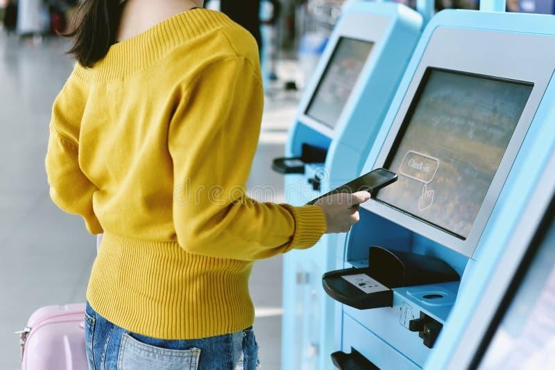 Reiziger die zelf - controle gebruiken - in de dienst van de machinekiosk bij luchthaven stock afbeelding