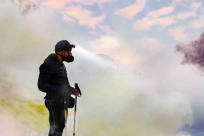 Reiziger in een gezichts beschermend masker in de krater van een vulkaan Zwavelwolken en roze zonsopgang Een gevaarlijke reis in  stock foto's