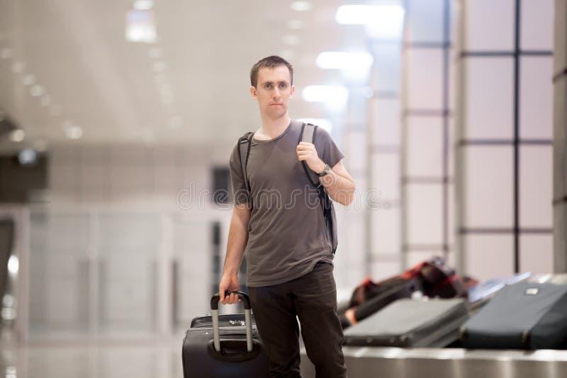 Reiziger met bagage bij transportband stock afbeelding
