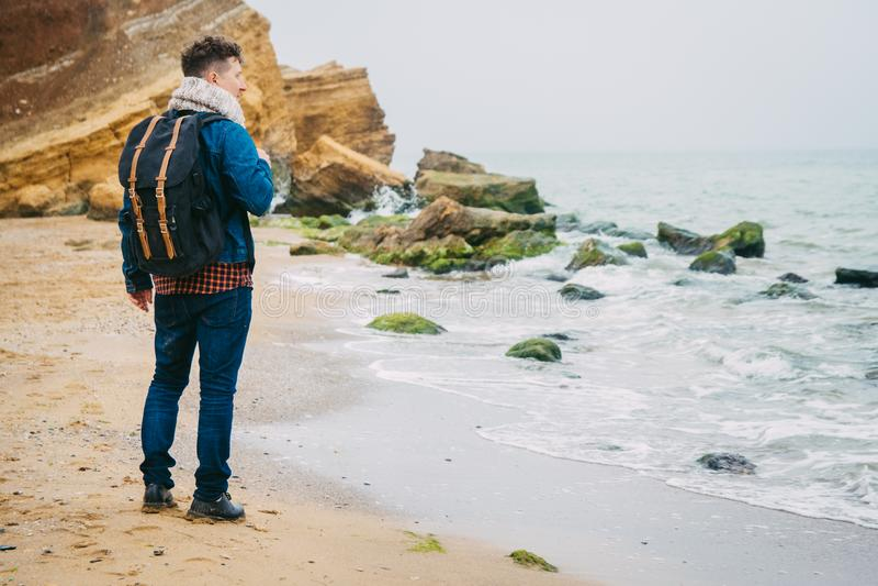 Reiziger met een rugzak die zich dichtbij een rots tegen een mooie overzees met golven, het modieuze hipsterjongen stellen dichtb stock fotografie
