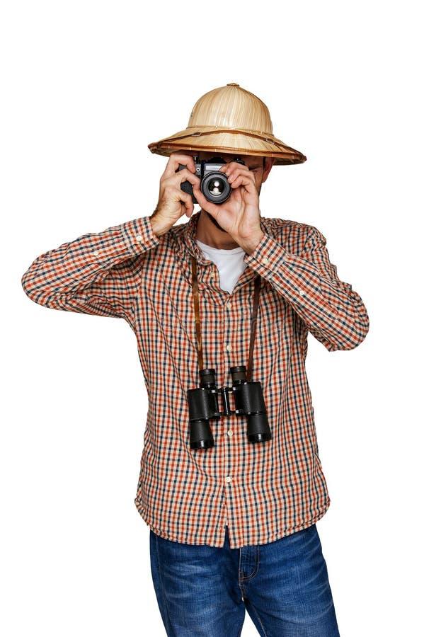 Reiziger met ontdekkingsreizigerhoed en wandelaaroverhemd met camera over wit wordt geïsoleerd dat stock foto's
