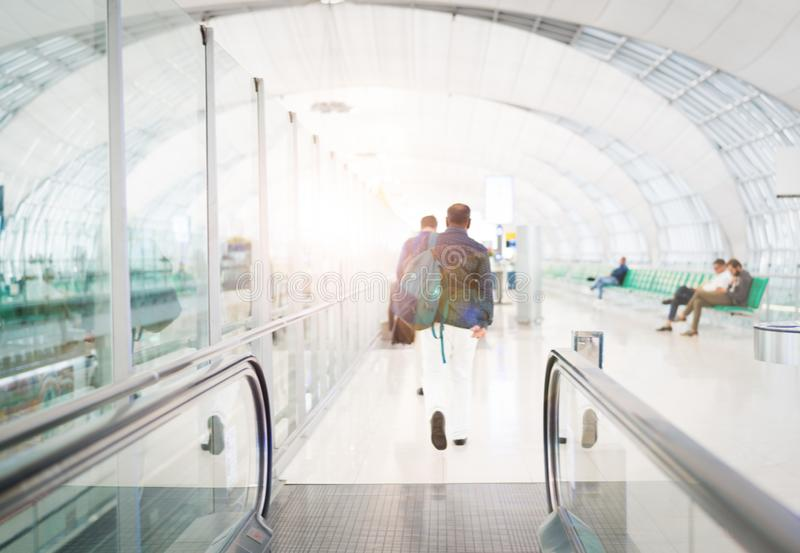Reiziger met reiszak of bagage die in de luchthaven eindgang lopen voor lucht het reizen De motie van het onduidelijke beeld stock afbeeldingen