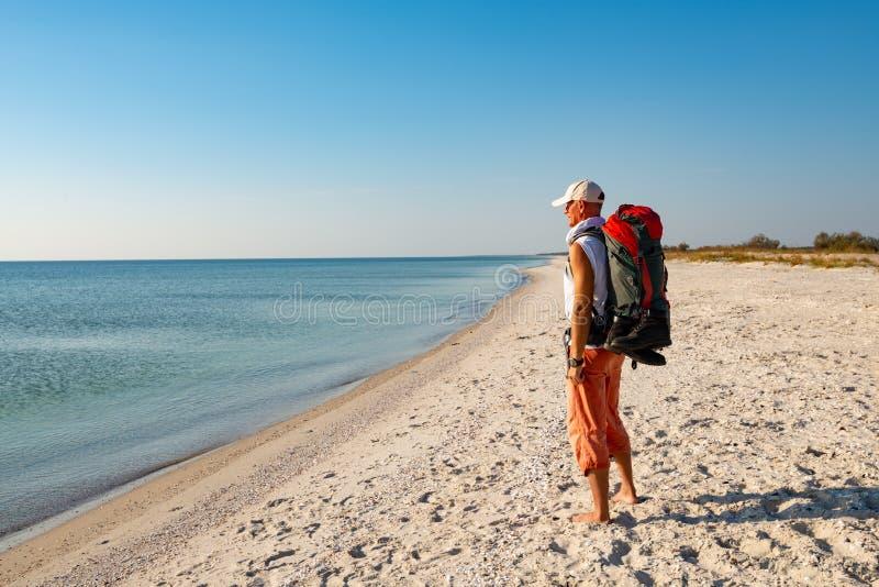 Reiziger met rugzaktribunes op het verlaten strand royalty-vrije stock foto