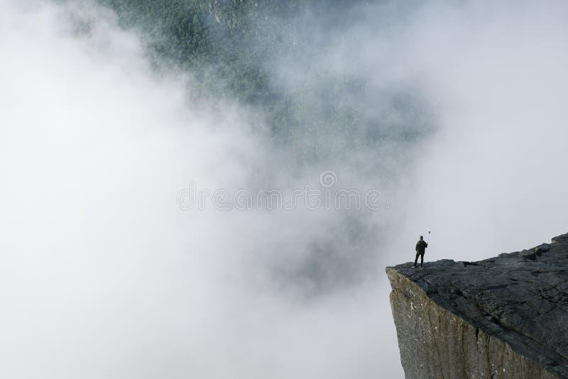 Reiziger op de Rots Preikestolen, Noorwegen stock foto