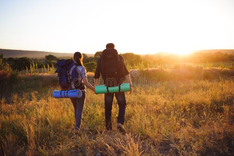 Reizigers die met rugzak in zonsondergang lopen Silhouetten van twee wandelaars die met rugzakken bij zonsondergang lopen stock fotografie