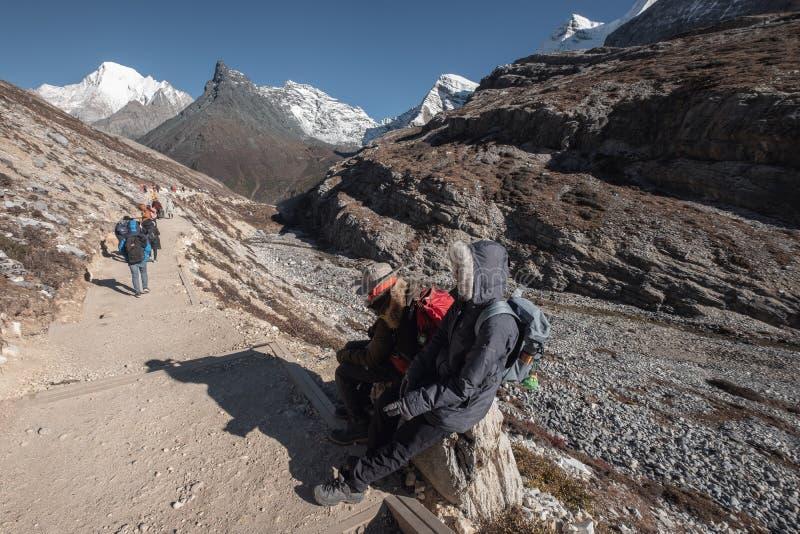 Reizigers die terwijl op rots met toeristentrekking in vallei bij Yading-natuurreservaat zitten stock foto's