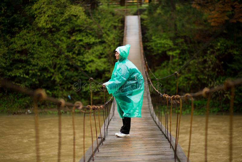 Reizigers hogere mooie vrouw in de blauwe dwarsrivier van het regenjasje door scharnierende brug in bos, die van stilte genieten stock foto's