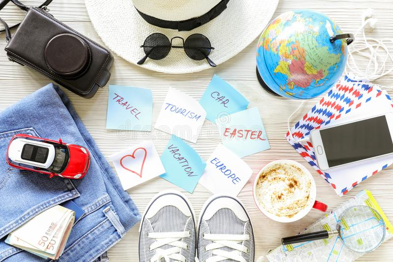 Reizigers` s toebehoren en punten, stickers met nota's over witte houten achtergrond, planningsreis van Europa door auto op Pasen stock afbeelding