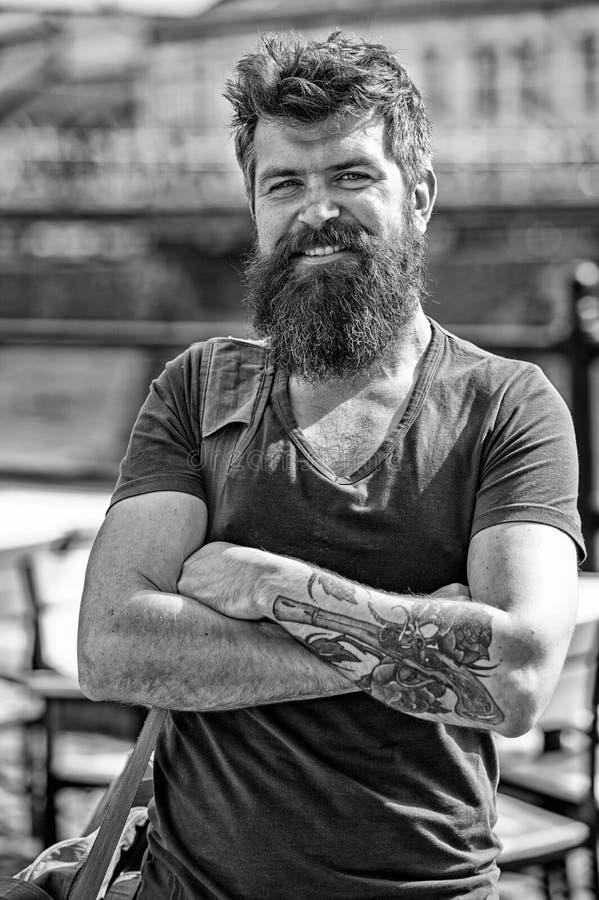 Reizigersconcept De mens met lange modieuze baard kwam bij stadscentrum aan Mens met baard op vrolijk gezicht, stedelijke achterg royalty-vrije stock foto's