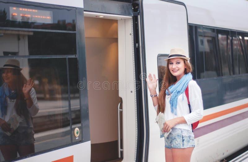 Reizigersmeisje die en een trein op spoorwegplatform wachten inschepen stock foto