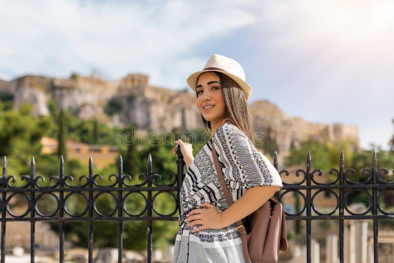 Reizigersmeisje die voor de Akropolis van Athene bezienswaardigheden bezoeken royalty-vrije stock fotografie