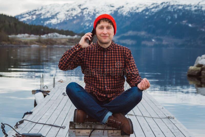 Reizigersmens die op mobiele telefoon spreken Toerist in een gele rugzak die zich op een achtergrond van een berg en een meer bev stock afbeeldingen