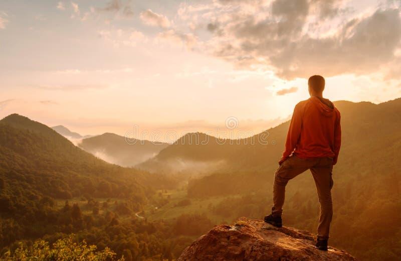 Reizigersmens die zich bovenop rots in de bergen bevinden stock foto