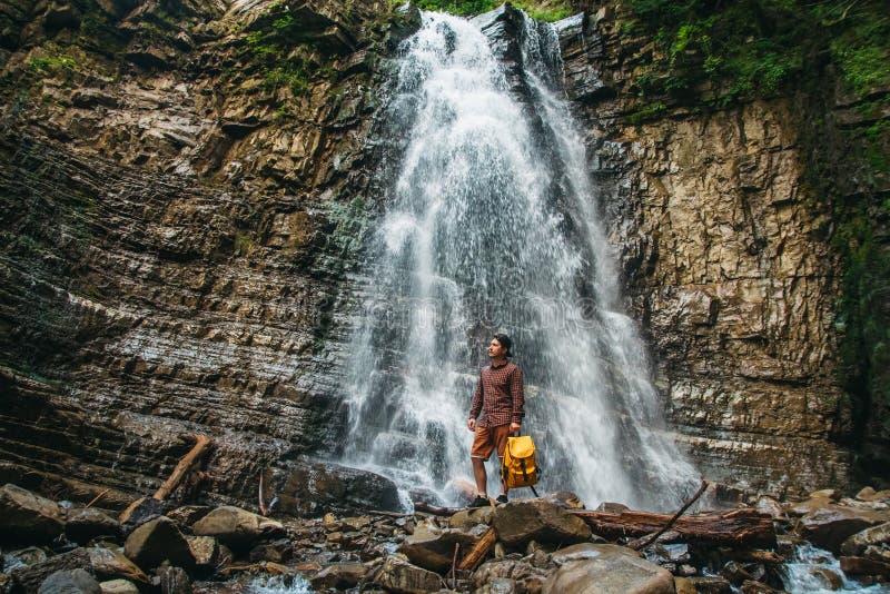 Reizigersmens met een gele rugzak die zich op de achtergrond van een waterval bevinden Het Concept van de reislevensstijl stock fotografie