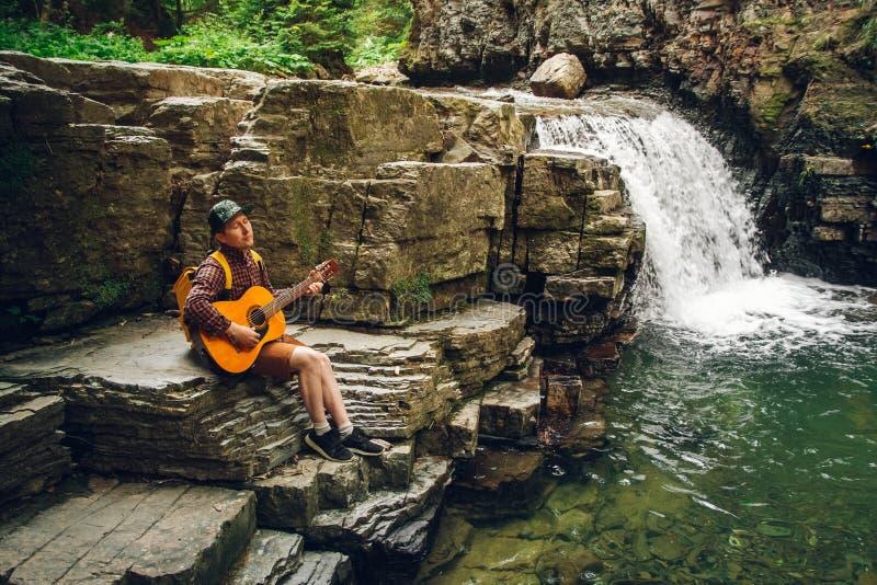 Reizigersmens met een rugzak het spelen gitaar tegen een waterval Ruimte voor uw sms-bericht of promotieinhoud royalty-vrije stock fotografie
