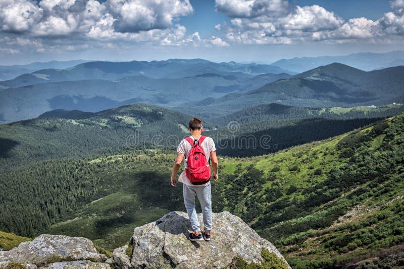 Reizigersmens met rode rugzak in bergen Het bos van de de zomermening, wolken stock foto