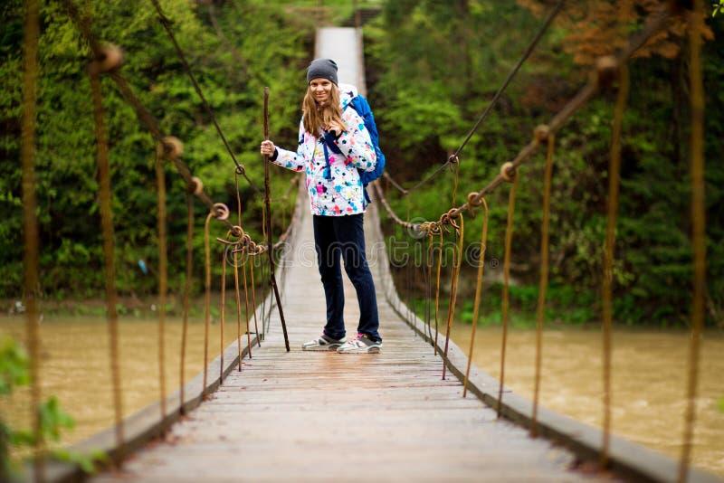 Reizigersvrouw die met rugzak in bos lopen die Rivier kruisen stock fotografie