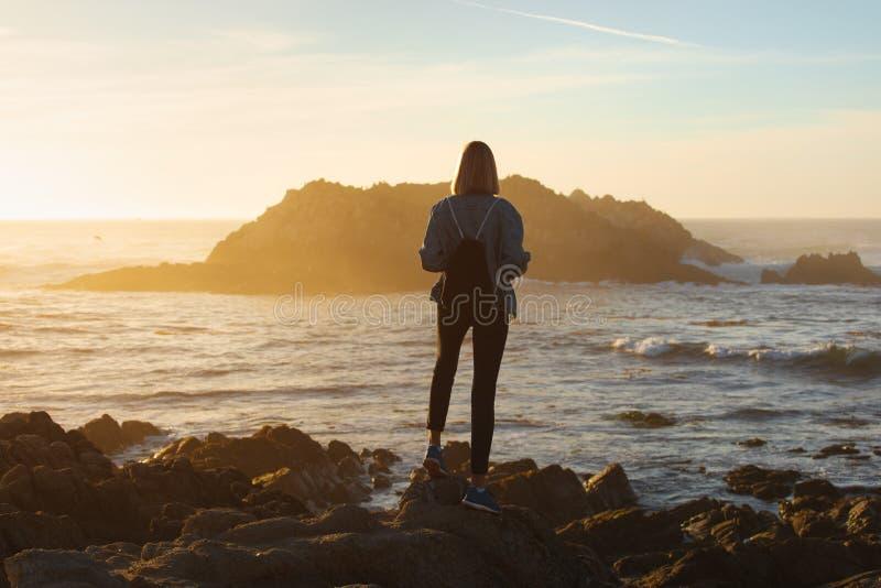 Reizigersvrouw die met rugzak van oceaanmening, meisjeswandelaar bij zonsondergang, reisconcept, Californië, de V.S. geniet royalty-vrije stock foto's