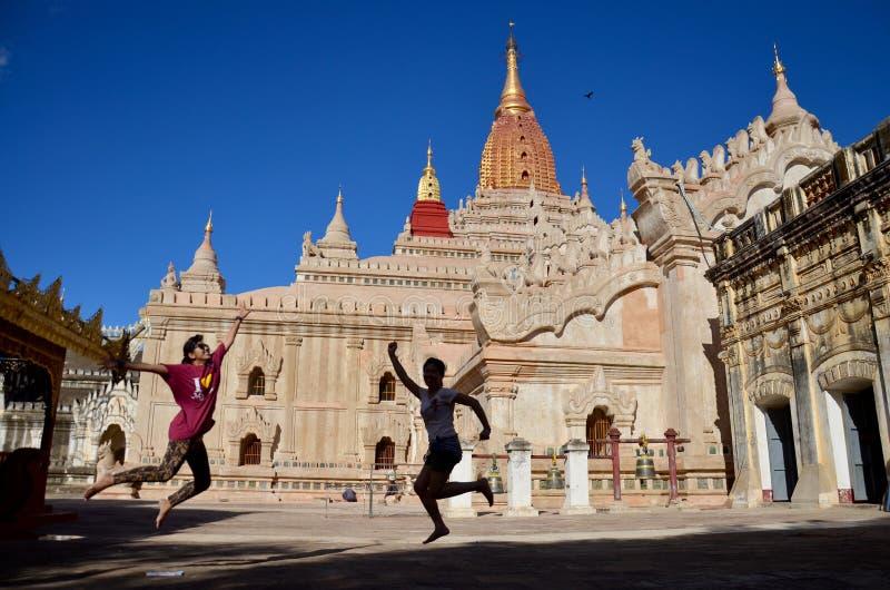 Reizigersvrouwen die bij Ananda-tempel in Bagan, Myanmar springen stock foto's