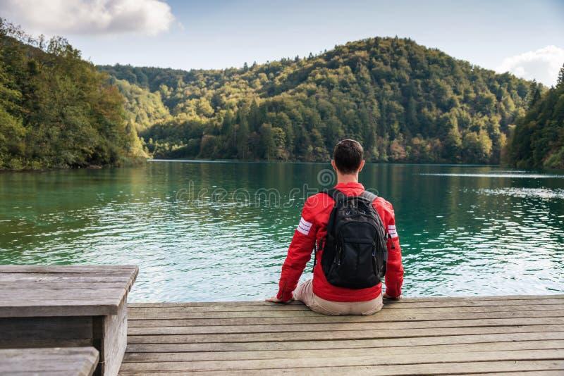 Reizigerszitting door het meer royalty-vrije stock fotografie