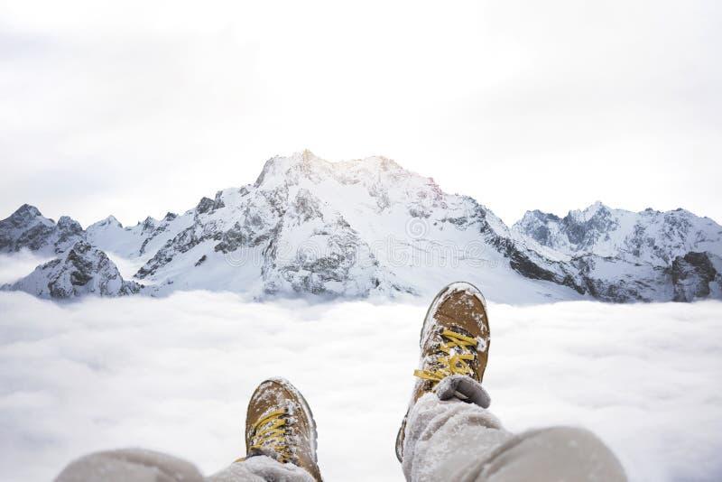 Reizigerszitting op bergpiek, POV-mening op grote de winterbergen boven de wolk en wandelingslaarzen stock afbeelding