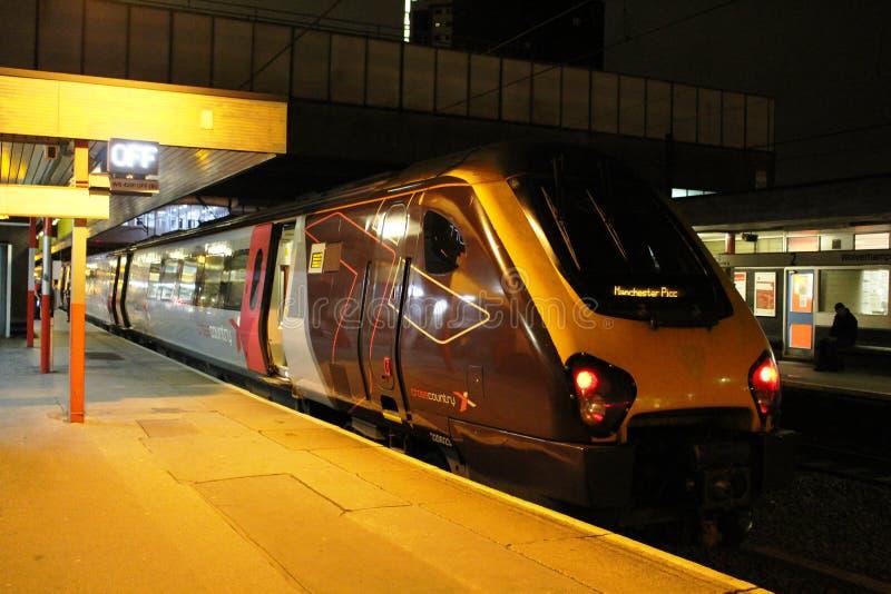 Reizigertrein bij de post van Wolverhampton bij nacht stock foto's