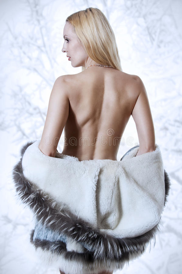 Reizvolle blonde Frau in der Pelzmantelrückseite stockfotografie