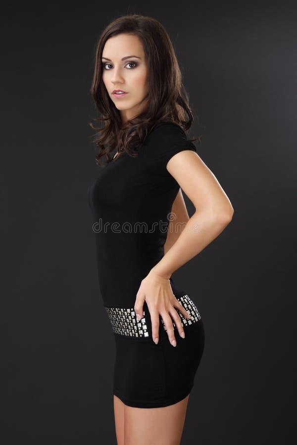 Reizvolle Brunettefrau, die im schwarzen Kleid aufwirft lizenzfreies stockbild