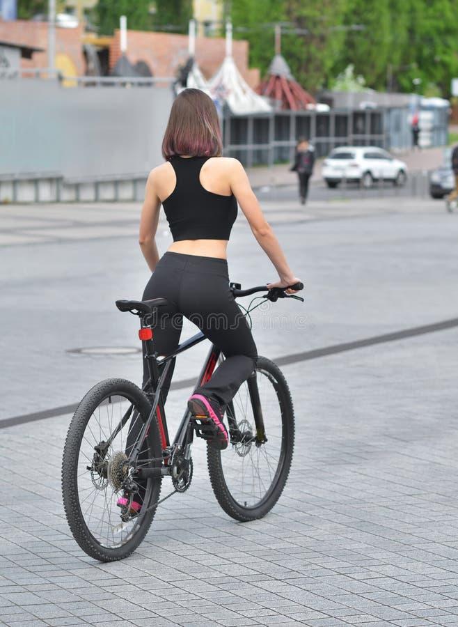 Reizvolle Eignung Junge Schönheit in der schwarzen Sportabnutzungsaufstellung im Freien auf dem Fahrrad am Stadion lizenzfreie stockbilder