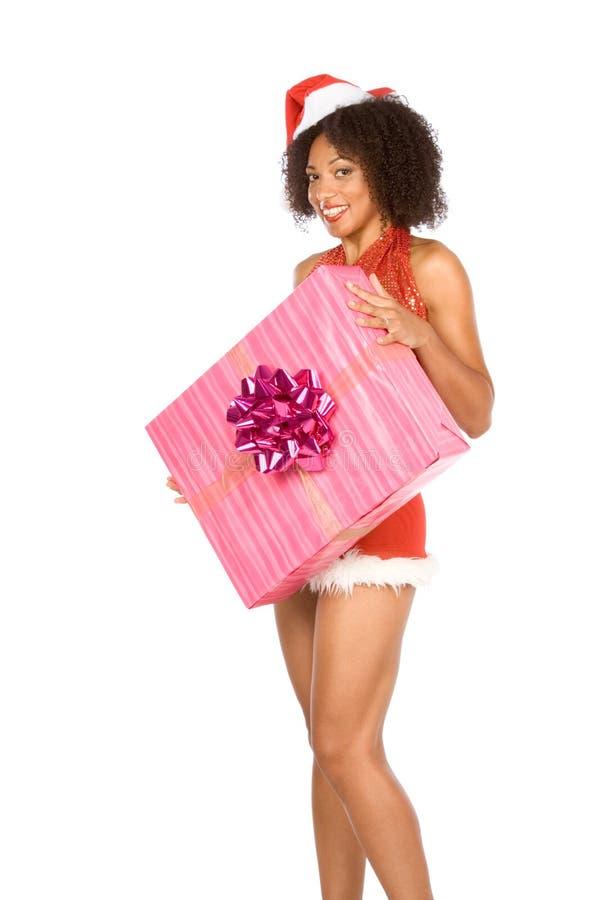 Reizvolle ethnische Frau im Hut mit Weihnachtsgeschenk lizenzfreies stockfoto