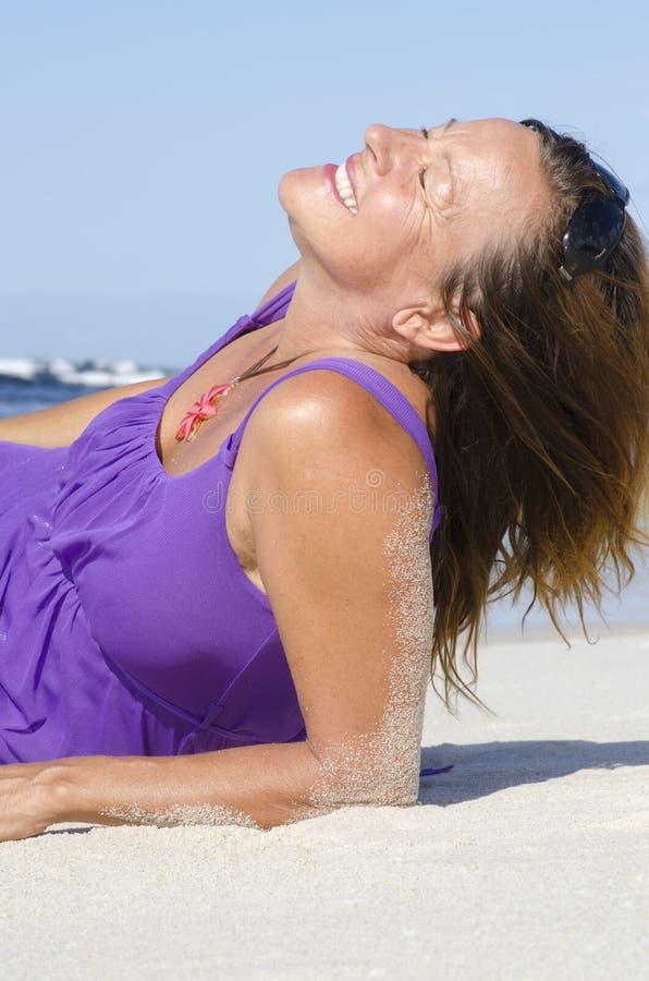 Reizvolle fällige Frau, die auf Strand sich entspannt stockbild