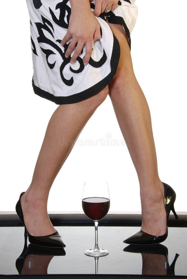 Reizvolle Fahrwerkbeine mit Glas Rotwein stockbilder