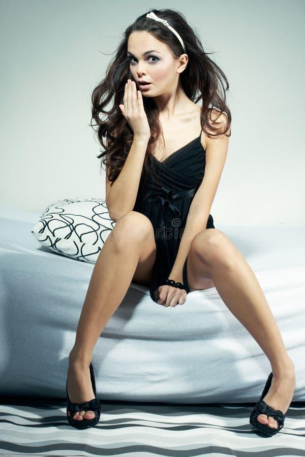 Reizvolle Frau, die auf Bett sitzt lizenzfreies stockbild